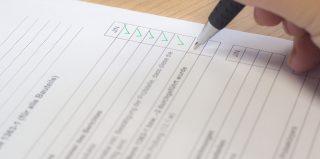 Un main tenant un stylo et cochant des cases sur un document