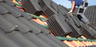 Couvreur qui rénove une toiture avec des tuiles noires