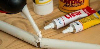 personne réparant un tube en plastique avec de la colle polymère